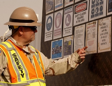 A male worker looking and pointing on his workplace safety reminders