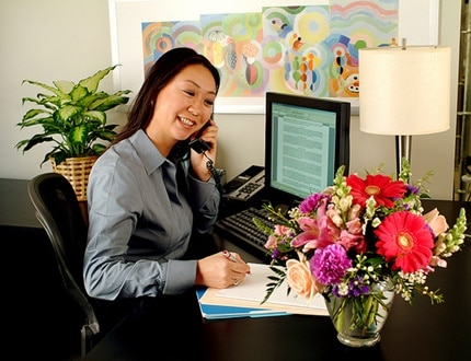 A happy female employee working at her office with green plants and fresh flowers