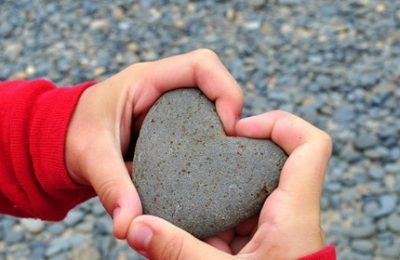 Two hands holding a heart formed stone