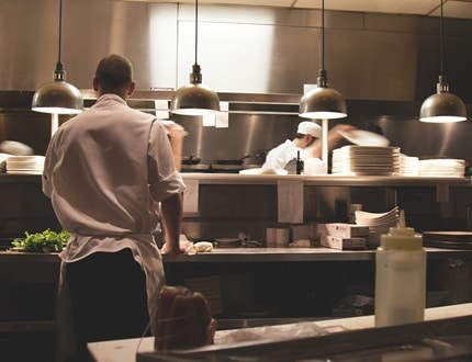 A chef inside the busy restaurant kitchen