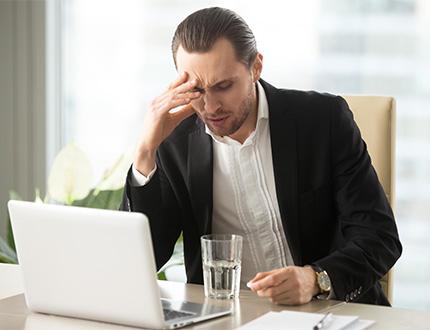 male employee experiencing head ache
