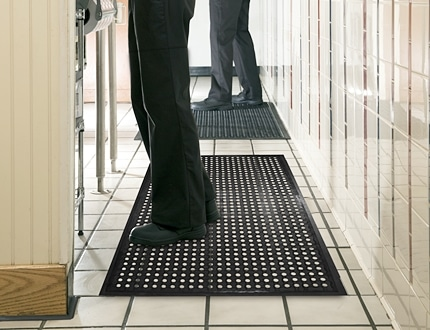 Employees stepping on the black anti fatigue mats