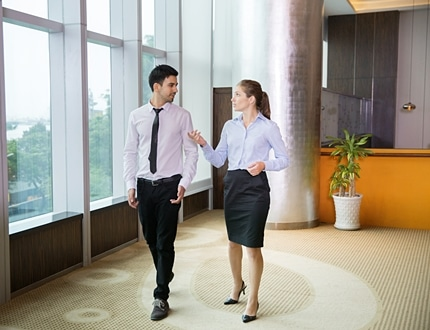 Two young female and male business people discussing something and walking along window in office.