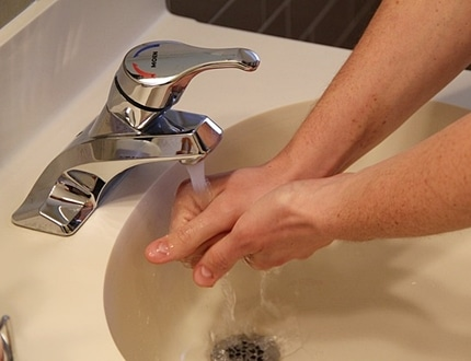 person washing hands with a flowing water