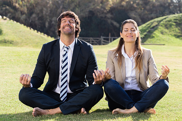 adult man and woman performing a yoga post outdoors