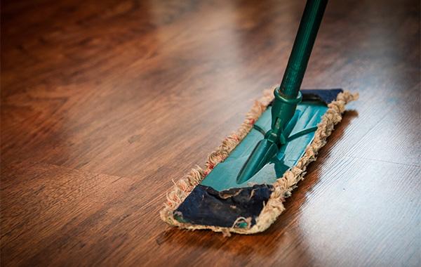 green floor mop and a shiny mahogany floor