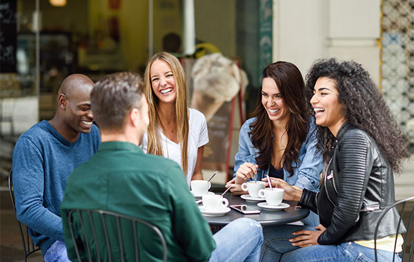 happy group of young adult talking in a cafe
