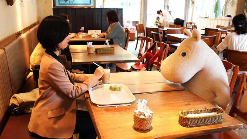 Japanese woman dining in front of a stuffed animal