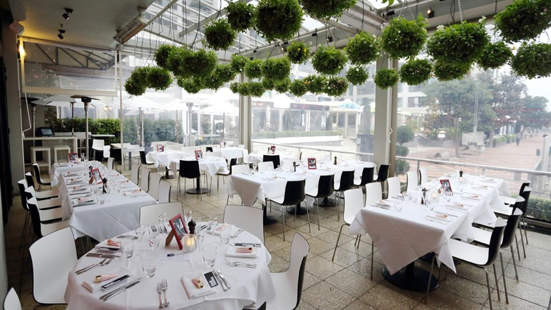 elegant white and black themed open window restaurant with green hanging plants
