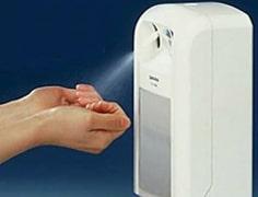 person using a white hand sanitiser dispenser