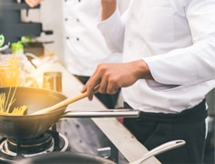 chef wearing a white uniform cooking pasta