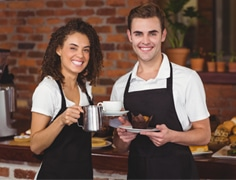 happy male and female cafe staff wearing black apron