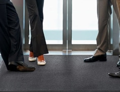 employee stepping on a black entrance mat