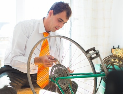 A man holding his bicycle wheel