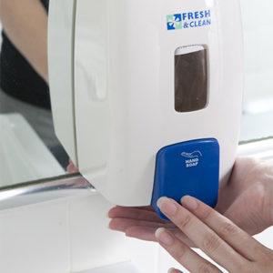 person using the white soap dispenser
