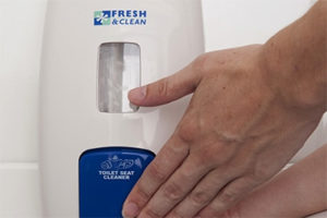 person dispensing toilet seat cleaner from a white dispenser