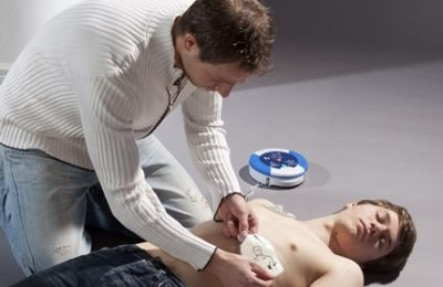 First aider using automated external defibrillator (AED) on casuality