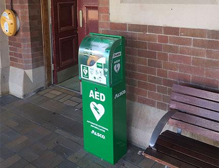 Alsco green AED positioned beside the door
