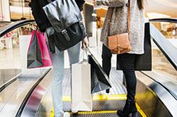 two women carrying shopping bags and using escalator