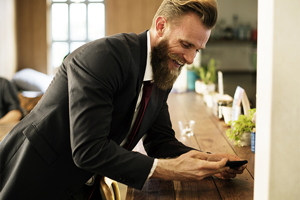 happy male employee using his mobile phone
