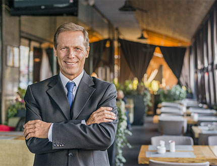 adult man wearing corporate attire standing inside the restaurant