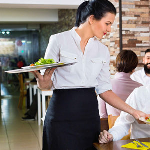 waitress wearing white long sleeve and black apron serving the food