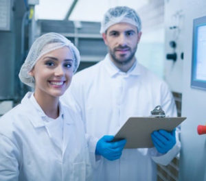 Man and woman wearing white food processing uniform