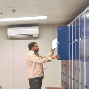 man placing a white hard hat in a blue locker