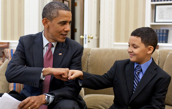 President Obama bumps his hands to a young boy