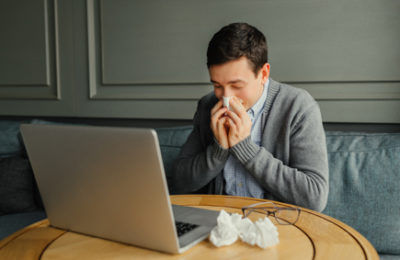 Young business man blows his nose while working at his laptop